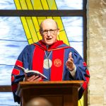 United Theological Seminary President Dr. Kent Millard preaching on an altar in full doctoral regalia