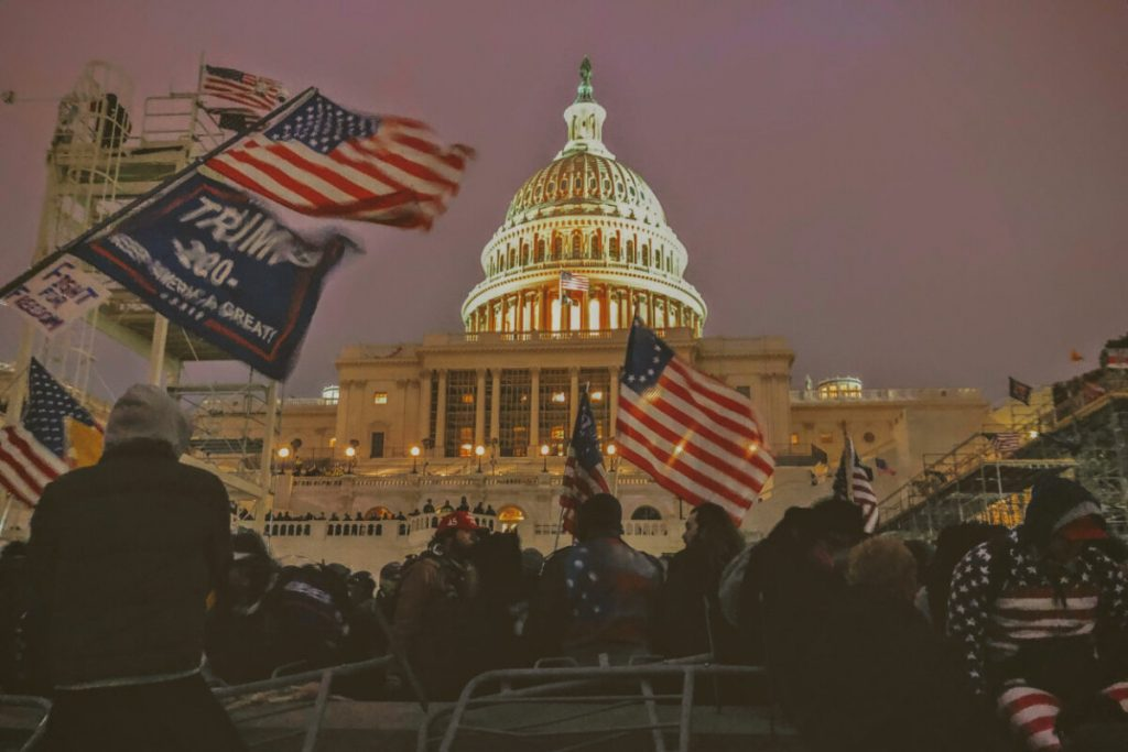 A large crowd gathered in front of the US Capitol. American flags, Trump 2020 campaign flags, and a colonial flag are prominent against the lighted building and early evening sky.